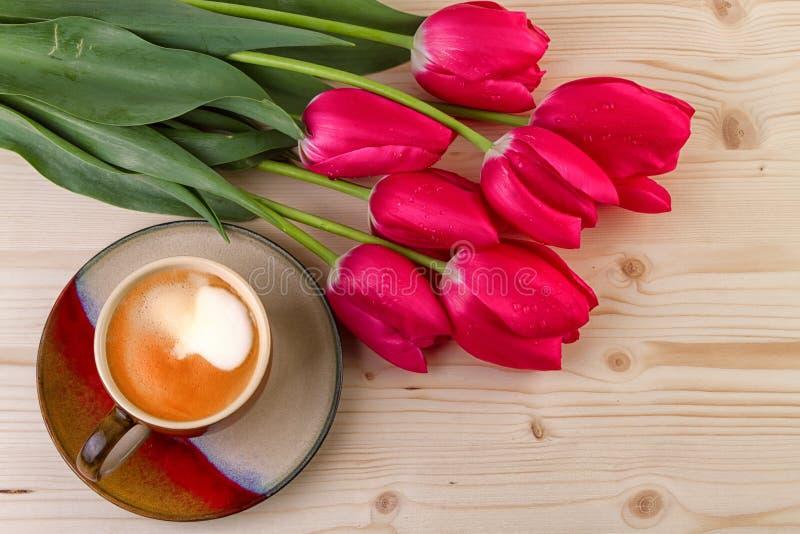 Чашка кофе с красными тюльпанами стоковое фото rf