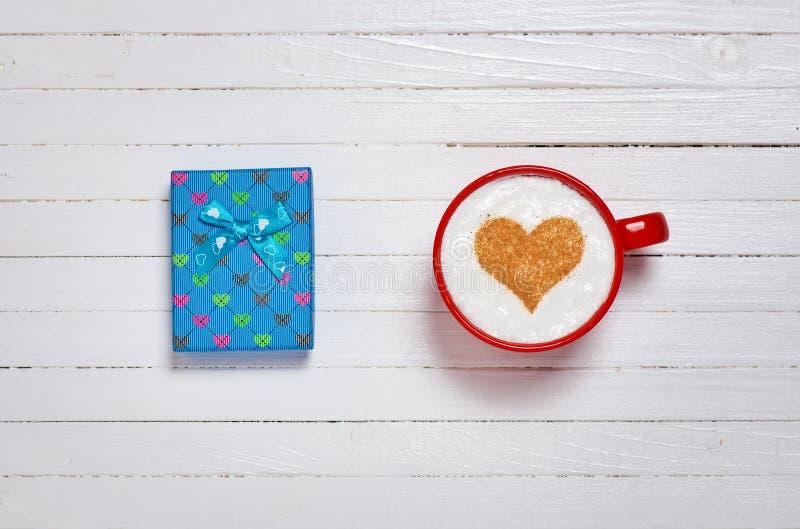 Чашка кофе с символом и подарочной коробкой формы сердца стоковое фото rf