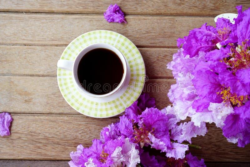 Чашка кофе с цветком весны фиолетовым на деревянной предпосылке стоковые изображения rf