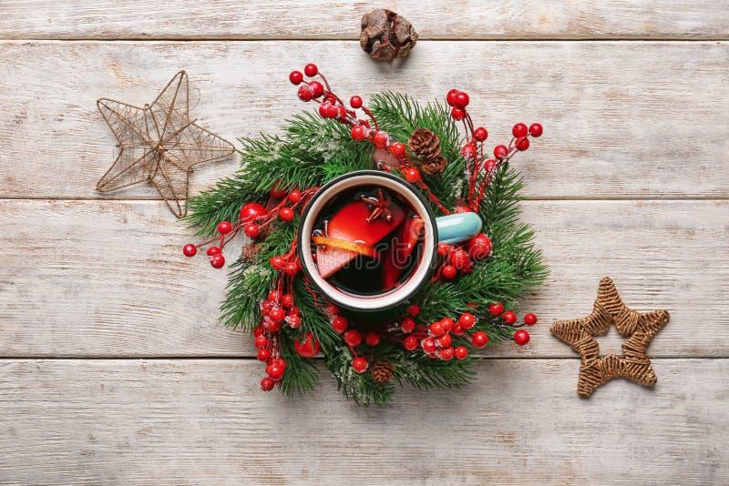 Чашка металла очень вкусного обдумыванного вина с венком рождества на светлом деревянном столе стоковое изображение rf