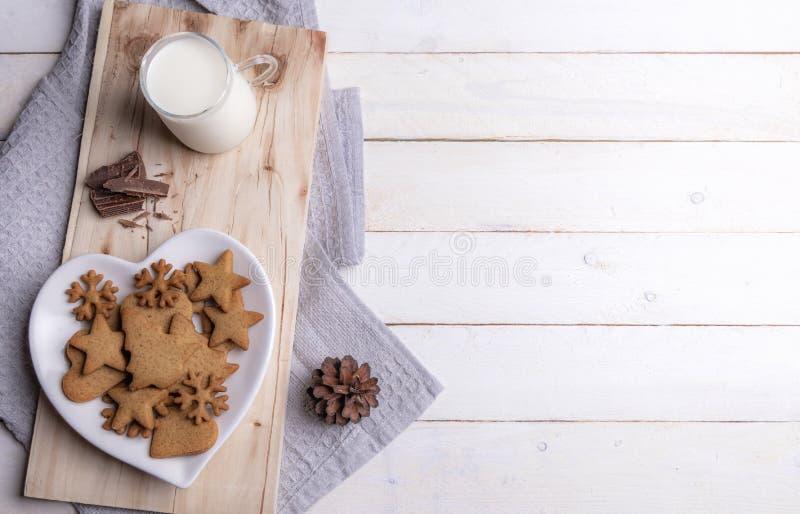 Чашка молока и печений рождества на белой таблице стоковые изображения rf