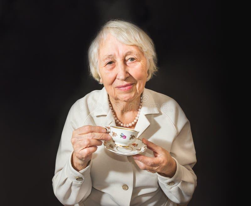 чашка наслаждаясь старшей женщиной чая стоковая фотография rf