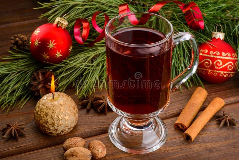 Чашка обдумыванного шарика вина, свечи и рождества стоковое изображение