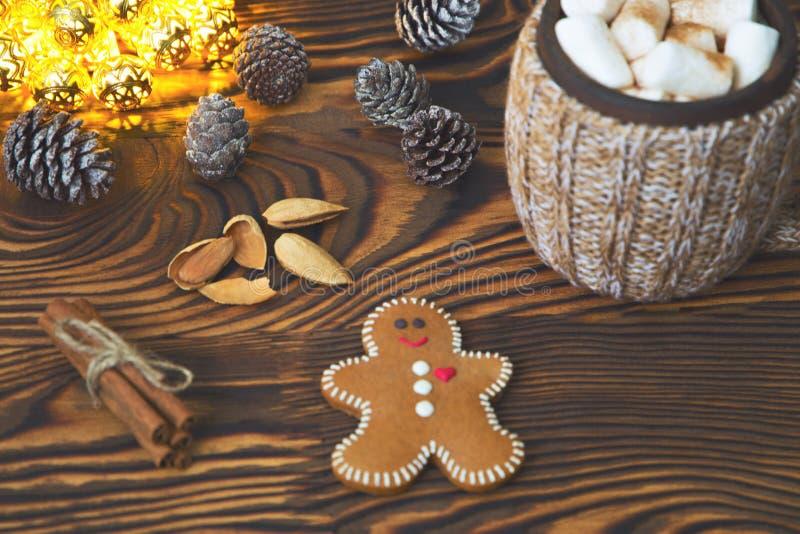 Чашка питья с зефиром и вкусным печеньем пряника на предпосылке светов и сосен рождества стоковые фото