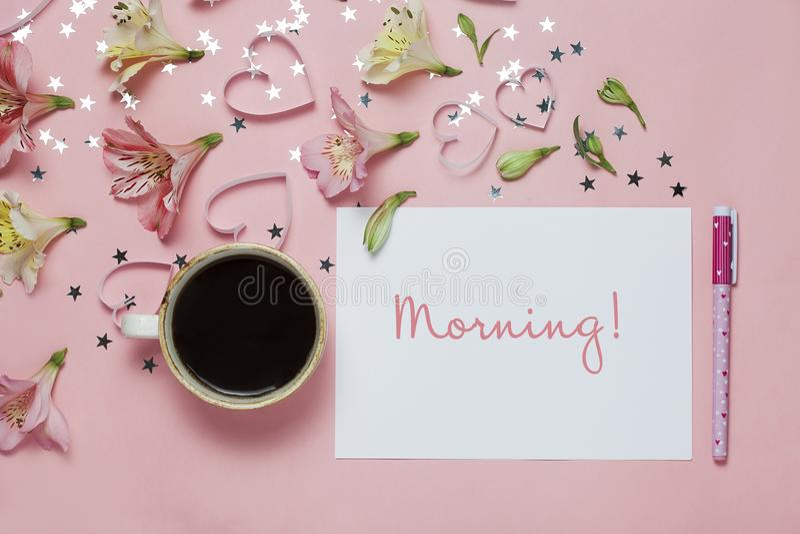 Чашка приветствия coffe и весны с ручкой, состав цветка и утро слова на розовой предпосылке Взгляд сверху, плоское положение стоковое изображение rf