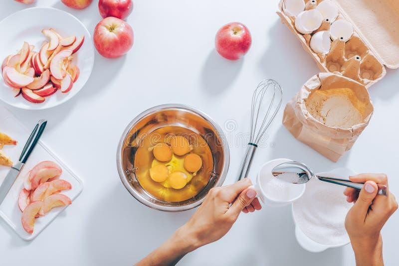 Чашка рук женщины измеряя сахара, который нужно смешать ее с яйцами стоковая фотография rf
