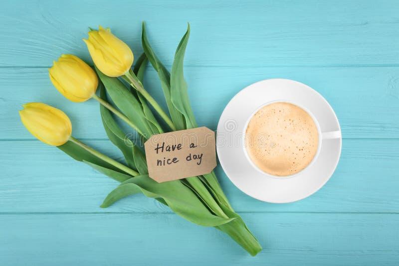 Чашка свежего кофе с желтыми тюльпанами и карточкой стоковая фотография