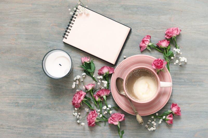 Чашка сметанообразных кофе, блокнота и цветков стоковые изображения rf