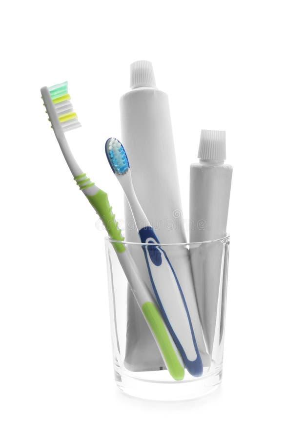 Чашка с зубными щетками и затиром на белой предпосылке стоковое изображение