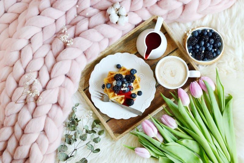 Чашка с капучино и домодельными бельгийскими waffles с соусом клубники и ягодами, розовым пастельным гигантским одеялом стоковая фотография rf