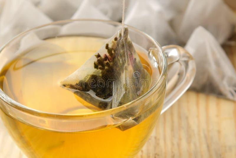 Чашка с пирамидой чая и пакетика чая Конец-вверх На деревянной таблице стоковое изображение