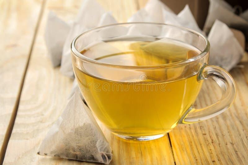 Чашка с пирамидой чая и пакетика чая Конец-вверх На деревянной таблице сделать чай стоковая фотография