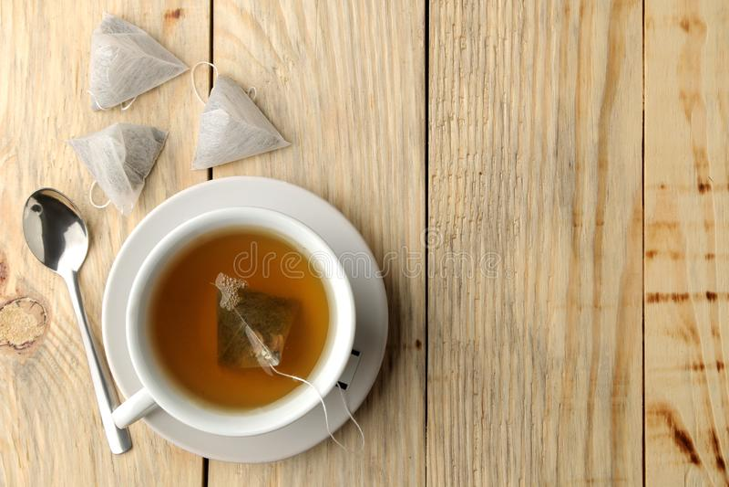 Чашка с пирамидой чая и пакетика чая Конец-вверх На деревянной таблице сделать чай стоковое фото rf