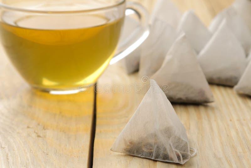 Чашка с пирамидой чая и пакетика чая Конец-вверх На деревянной таблице сделать чай стоковое изображение