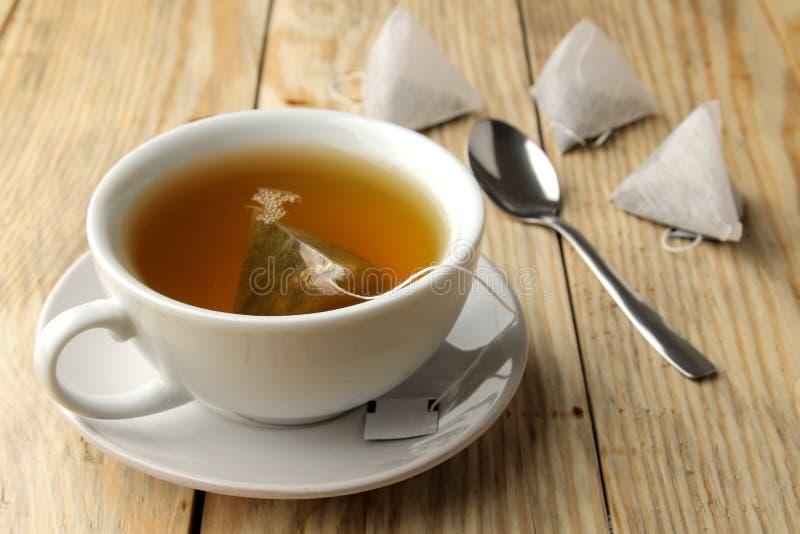 Чашка с пирамидой чая и пакетика чая Конец-вверх На деревянной таблице сделать чай стоковые фотографии rf