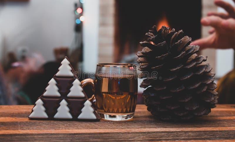 чашка теплого конуса чая и сосны с шоколадом в форме рождественской елки на деревянной доске стоковое фото rf