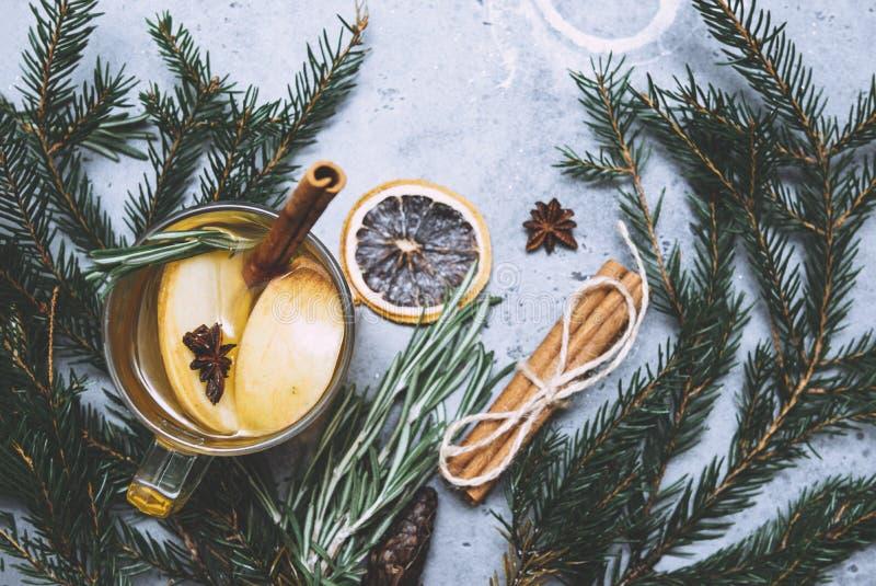 Чашка фруктового чая с лимоном и яблоком, звездным анизом, ветвями корицы, розмари, кусочек сушеного оранжевого на сером стоковые фотографии rf