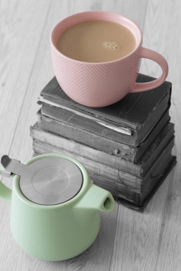 Чашка чаю в розовой чашке с пастельным зеленым чайником и стог старых книг, с выборочным цветом стоковые изображения rf