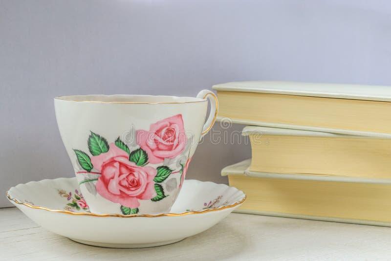 Чашка чаю в чашке фарфора и поддоннике и стоге книг стоковые изображения