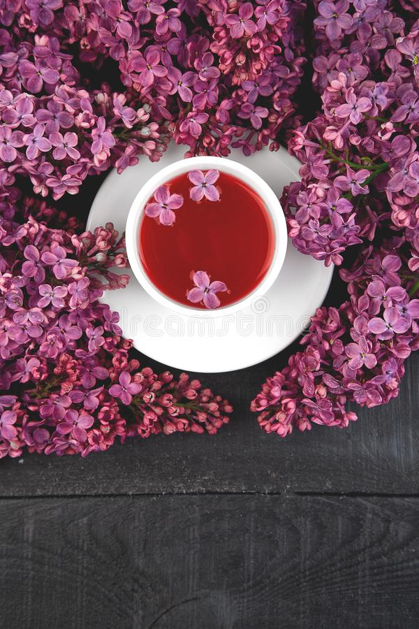 Чашка чаю и ветви сирени букета цветков зацветая стоковое изображение rf
