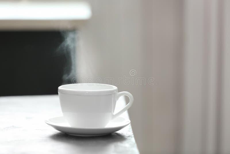 Чашка чаю и поддонник на таблице стоковые фото