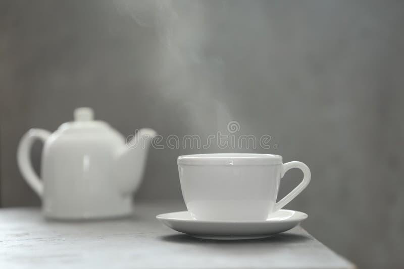Чашка чаю и поддонник на таблице стоковые изображения