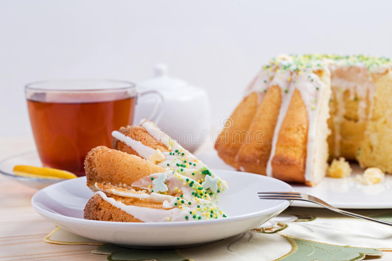 Чашка чаю и торт на tableware фарфора на вышитой скатерти с daffodil стоковые изображения rf