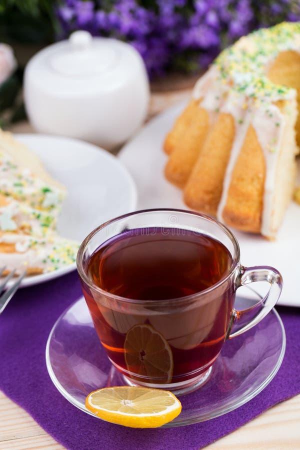 Чашка чаю и торт на tableware фарфора на фиолетовой скатерти стоковая фотография rf
