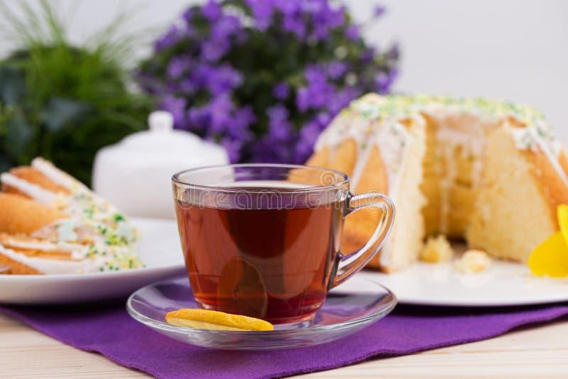 Чашка чаю и торт на tableware фарфора на фиолетовой скатерти стоковое фото