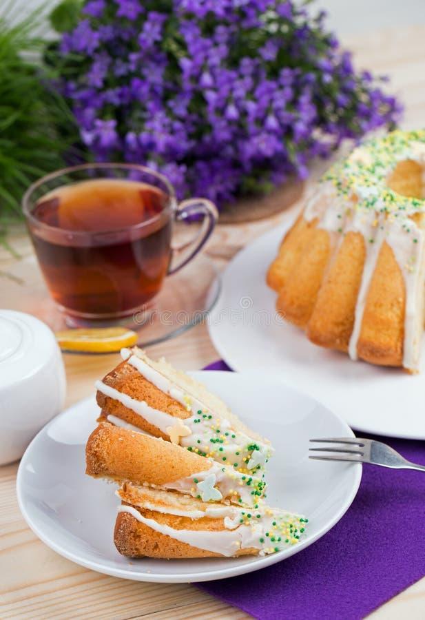 Чашка чаю и торт на tableware фарфора на фиолетовой скатерти стоковое фото rf