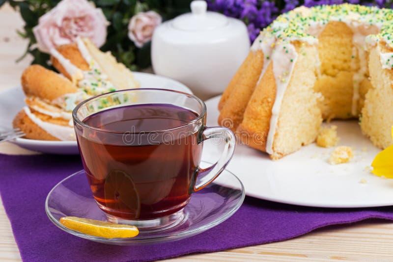 Чашка чаю и торт на tableware фарфора на фиолетовой скатерти стоковые фото