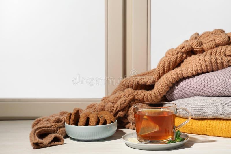 Чашка чаю и шар с печеньями на windowsill, космосе для текста Питье зимы стоковые фотографии rf