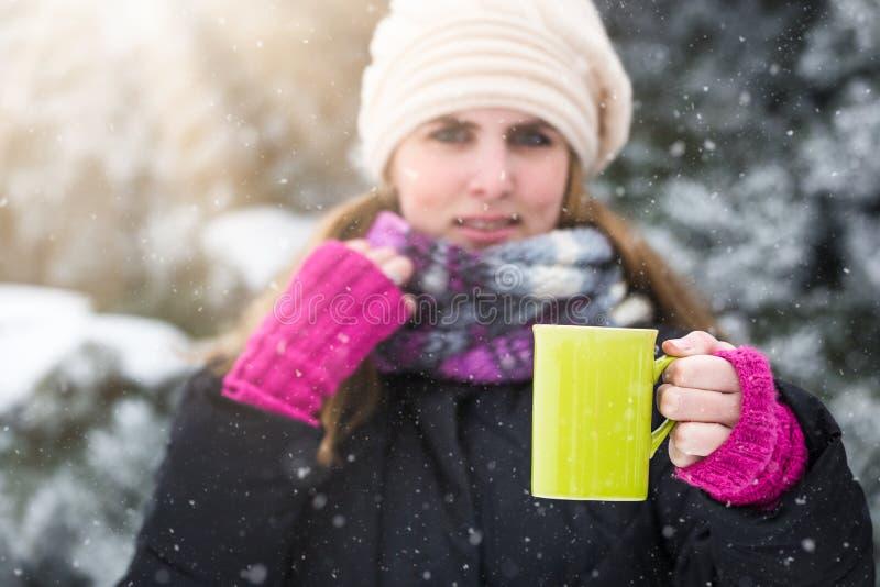 Чашка чаю показа молодой женщины в парке или древесины покрытые со снегом стоковое изображение rf