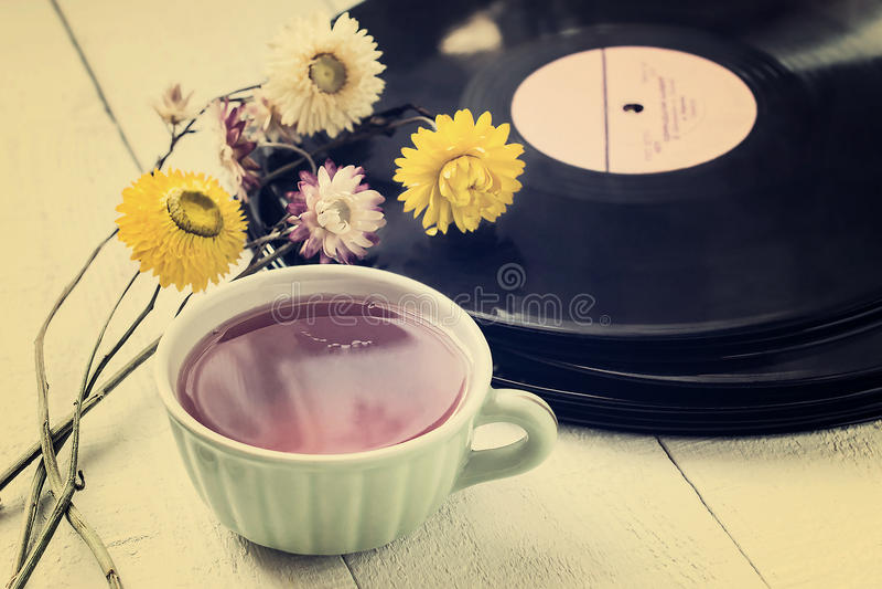 Чашка чаю, старые показатели винила и сухие цветки стоковые изображения rf
