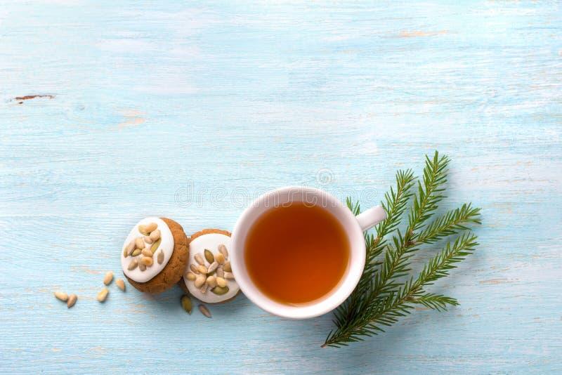 Чашка чаю с душистыми пряниками рождества меда с поливой и гайками, с ветвями рождественской елки и специями стоковые изображения rf