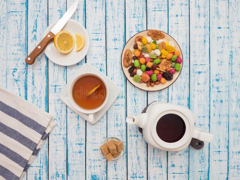 Чашка чаю с лимоном, чайником и высушенными плодоовощами на деревянном столе стоковые фото