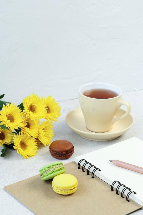 Чашка чаю, macaroon и примечания на конкретной таблице стоковые фотографии rf