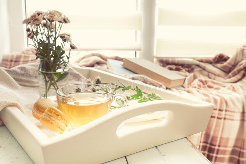 Чашка чаю, macaroons, цветки хризантемы и книги стоковое изображение rf