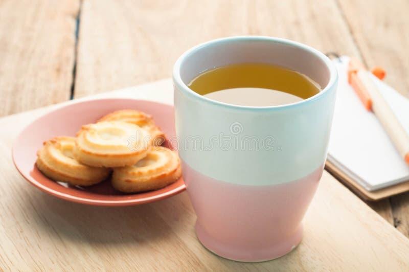 Чашка чая, печенье десерта на деревянном поле и бумага блокнота стоковое изображение rf