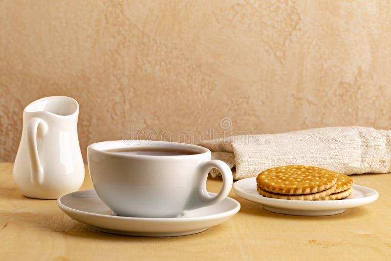 Чашка чая с горячим чаем на поддоннике и свежих печеньях стоковые изображения