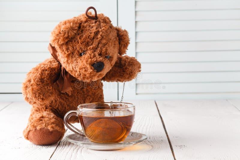 Чашка чая с плюшевым медвежонком, ослабляет время стоковое фото