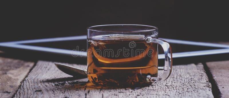Чашка черного горячего чая с ложкой и цифровой таблеткой на старом wo стоковая фотография