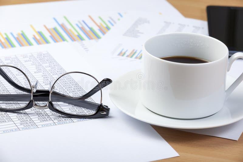 Чашка черного кофе и зрелищ на столе бухгалтера стоковое изображение