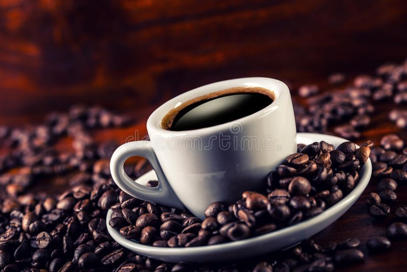 Чашка черного кофе и разлитых кофейных зерен стоковые фото