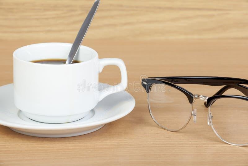 Чашка черного кофе на таблице с стеклами глаза стоковые фотографии rf