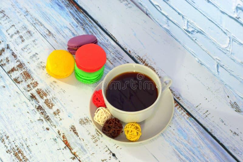 Чашка черного кофе с шариками для оформления и 4 пестротканых macaroons : стоковая фотография