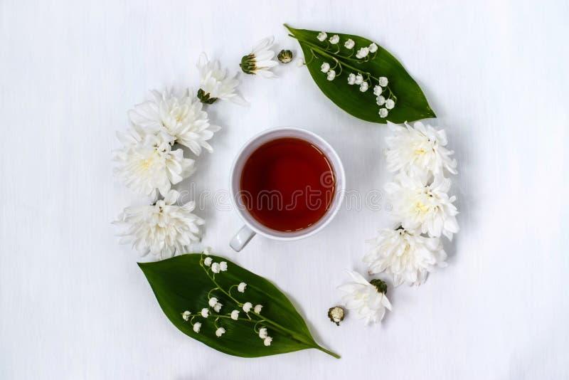 Чашка черного чая в круге хризантем и lilie цветков стоковое фото rf