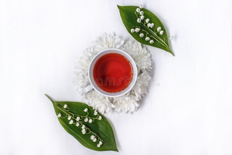 Чашка черного чая в круге хризантем цветков и лилии долины на белой предпосылке стоковое изображение