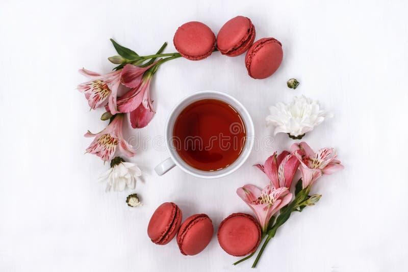 Чашка черного чая в круге Alstroemeria цветков и печений миндалины на белой предпосылке стоковые фотографии rf