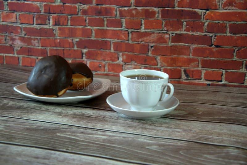 Чашка черного чая на поддоннике и плите с 2 donuts в лож замороженности шоколада на деревянном столе против кирпичной стены : стоковое изображение